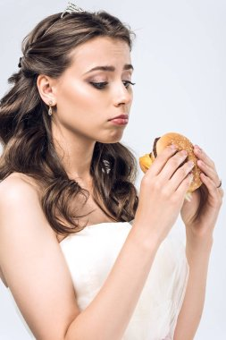 Sad young bride in wedding dress looking at burger in hands isolated on white stock vector