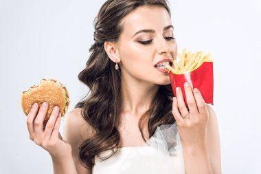 Young bride in wedding dress eating burger and french fries isolated on white stock vector