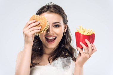 Happy young bride in wedding dress with burger and french fries isolated on white stock vector
