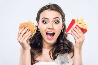 Close-up portrait of shocked young bride in wedding dress with burger and french fries looking at camera isolated on white stock vector