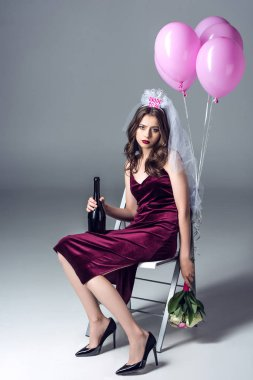 sad future bride in veil for bachelorette party sitting on chair with champagne and flowers and looking at camera after party on grey