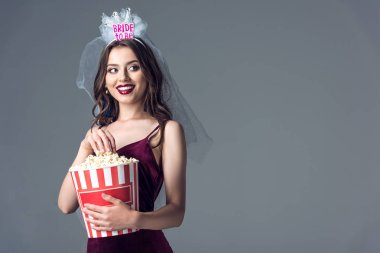 beautiful future bride in veil for bachelorette party eating popcorn isolated on grey