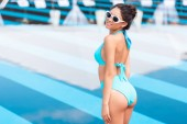 Fotografia ragazza abbronzata attraente che posa in bikini blu vicino alla piscina