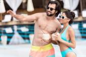 Fotografie junges Paar in der Sonnenbrille mit Kokosnuss Cocktails, Mann, zeigen etwas