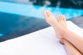 vista parziale dei piedi femminili sdraiato sul lettino a bordo piscina