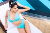 giovane donna in bikini prendere il sole sulle sdraio in piscina