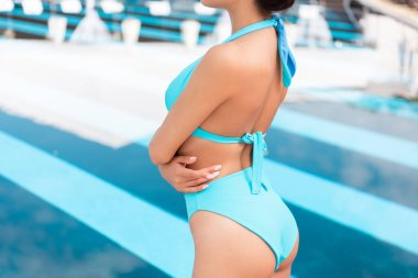 cropped view of girl posing in blue swimsuit near swimming pool