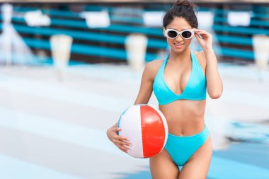 girl in sunglasses holding inflatable beach ball at poolside