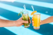 cropped view of couple holding glasses with fresh lemonades at swimming pool