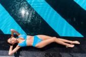 felülnézete a kék bikini napozásra a medence melletti lány
