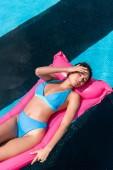 krásná holka v bikinách plovoucí na růžový nafukovací matraci v bazénu