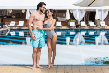 beautiful couple embracing near swimming pool at summertime