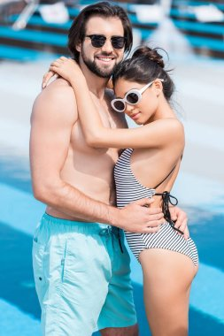 beautiful smiling couple in sunglasses embracing near swimming pool