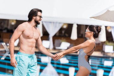 happy beautiful couple in sunglasses holding hands near swimming pool