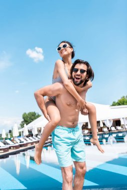 handsome man piggybacking his girlfriend near swimming pool