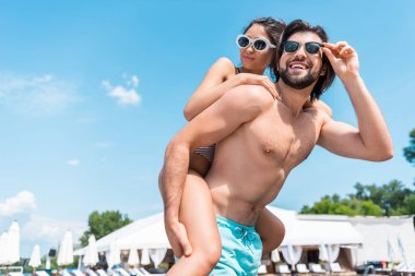 handsome boyfriend piggybacking his girlfriend on resort