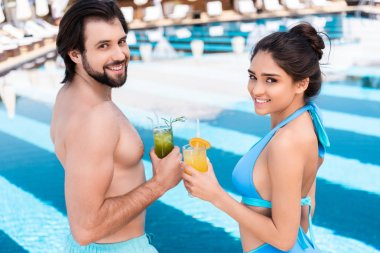 beautiful couple clinking with glasses of lemonade near swimming pool