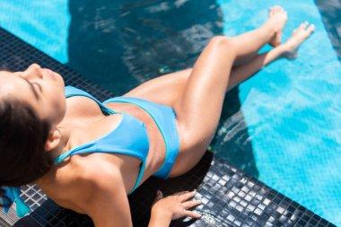 attractive girl in blue bikini sunbathing at swimming pool