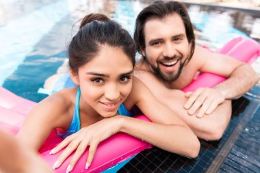 beautiful smiling couple swimming on pink inflatable mattress in pool and taking selfie