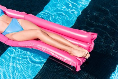 Low section view of girl resting on pink inflatable mattress in swimming pool stock vector