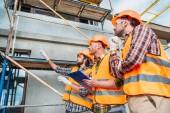 Fotografia gruppo di costruttori in caschi e giubbotti riflettenti che punta alla costruzione di casa