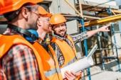 Close-up shot skupiny stavitelů vybavené koukal na staveništi