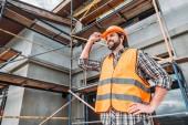 šťastný tvůrce v reflexní vestu a helmu stojící před stavba domu a hledat dál