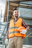 Fotografie happy builder in reflective vest holding helmet while standing in front of building house and looking away