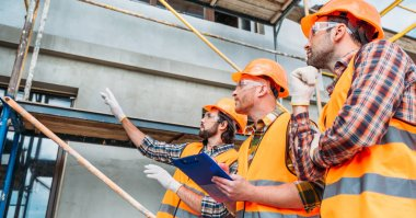 wide shot of group of builders in hard hats and reflective vests pointing at building house