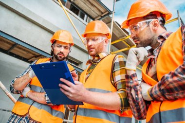 Bottom view of group of builders in hard hats and reflective vests looking at clipboard stock vector