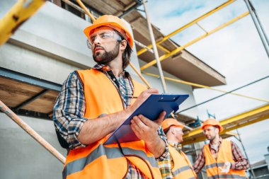 bottom view of handsome builder with clipboard looking away while his colleagues standing blurred on background