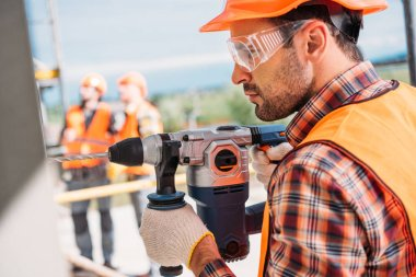side view of builder in protective helmet and eyeglasses using power drill at construction site