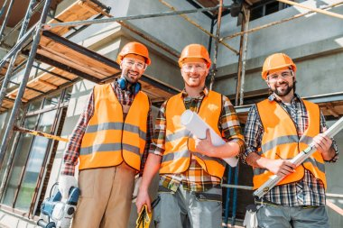 Bottom view of group of happy equipped builders looking at camera at construction site stock vector