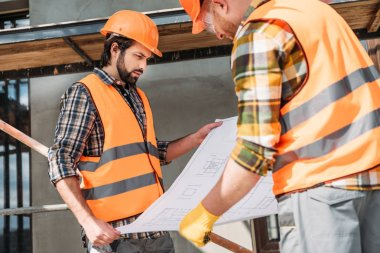 thoughtful builders with blueprint at construction site