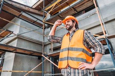 Happy builder in reflective vest and helmet standing in front of building house and looking away stock vector