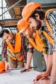 Skupina vážné, kteří se snaží vytvářet plán na staveništi