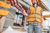 Oříznout záběr stavitelů v ochrannou vestu potřesení rukou na staveništi