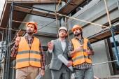 stavitelé a architekt koukal před staveniště