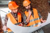 Fotografia premurosi costruttori fiduciosi al cantiere di lavoro con la cianografia