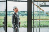 side view of handsome architect in suit and hard hat standing on terrace at construction site