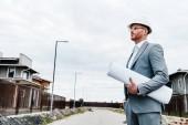 Fotografie pohledný architekt v obleku a s přilbou drží plánu při pohledu na dům