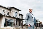 Fotografie pohledný architekt v obleku a přilbou stojící před dům