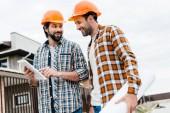 architekti s blueprint a tabletu pracují společně na staveništi