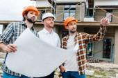 skupina architektů se stavebním plánu stojící před staveniště a hledat dál
