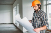 handsome smiling architect in plaid shirt and hard hat standing inside of building house with blueprint