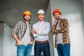Fotografie skupina architektů usmívající se v konstrukci budovy, při pohledu na fotoaparát