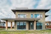 Fotografie fasáda z nedokončené moderní betonová budova se zelenou zahradou pod zamračenou oblohou