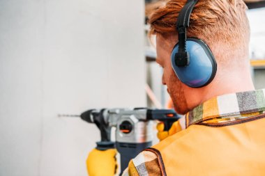 confident builder in noise reducing headphones using power drill at construction site