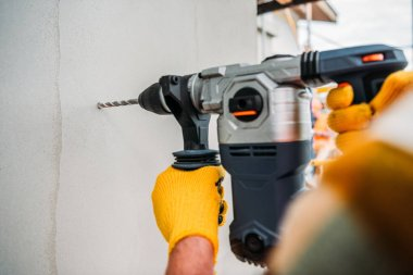 cropped shot of builder using power drill at construction site