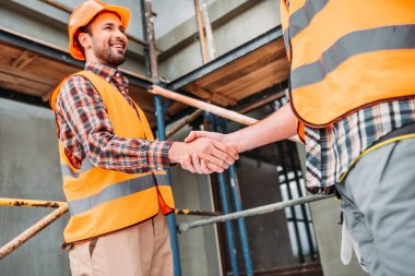 cropped shot of builders shaking hands at construction site